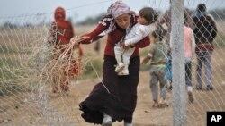 지난해 10월 시리아 코바니에서 피난한 쿠르드족 난민 여성이 아기를 안고 터키와 시리아 국경지역 루크 난민 캠프에서 불을 지필 나뭇가지를 줍고 있다. (자료사진)