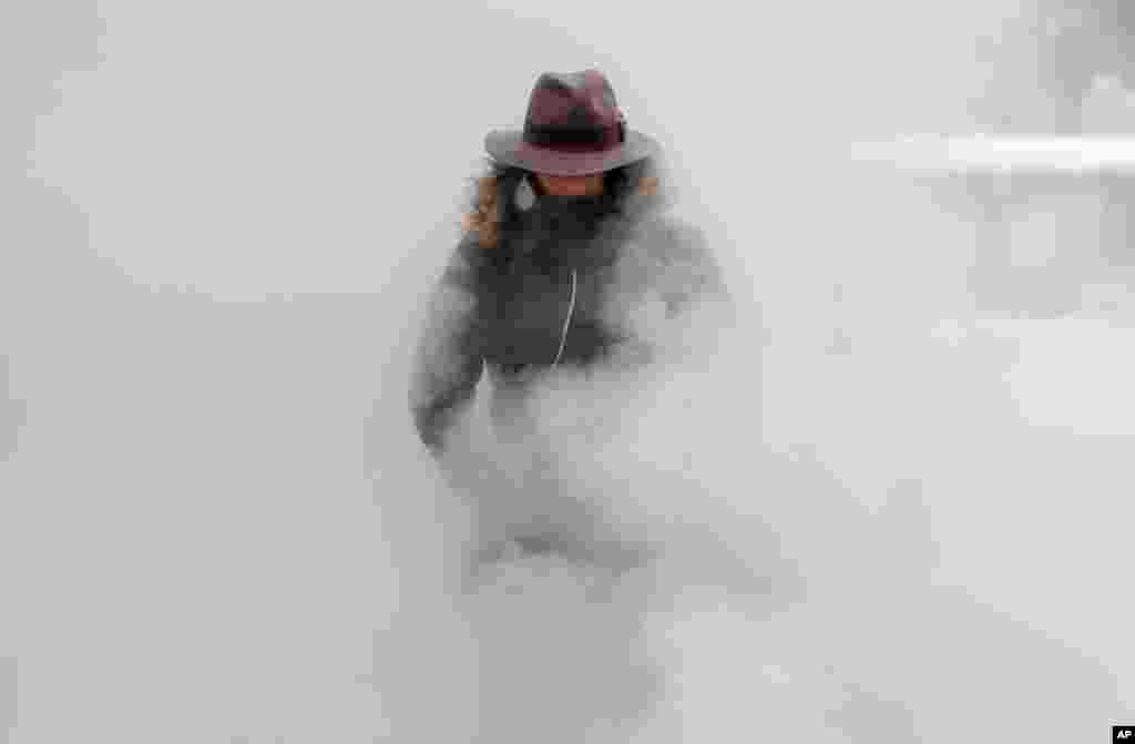 A woman walks through steam from an underground ventilation, as temperatures dropped below -20°C (- 4°F) in Bucharest, Romania.