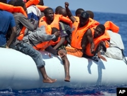 FILE - Migrants wearing life vests float in an inflatable boat during a rescue operation from the Aquarius vessel of SOS Mediterranee NGO and MSF (Doctors Without Borders) in the sea some 25 Nautical miles (29 miles, 46 kilometers) north of the Libyan coa