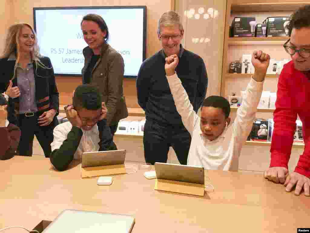 នាយកប្រតិបត្តិក្រុមហ៊ុន Apple លោក Tim Cook (ខាងឆ្វេង) ចូលរួមនៅក្នុងកម្មវិធីមួយសម្រាប់ឲ្យសិស្សរៀនសរសេរកូដកុំព្យូទ័រនៅឯហាងលក់ផលិតផលក្រុមហ៊ុន Apple មួយនៅក្រុង Manhattan នៅបុរីញូវយ៉ក នាថ្ងៃទី០៩ ខែធ្នូ ឆ្នាំ២០១៥។