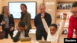 Apple Chief Executive Officer Tim Cook (C) attends an event for students to learn to write computer code at the Apple store in the Manhattan borough of New York December 9, 2015.