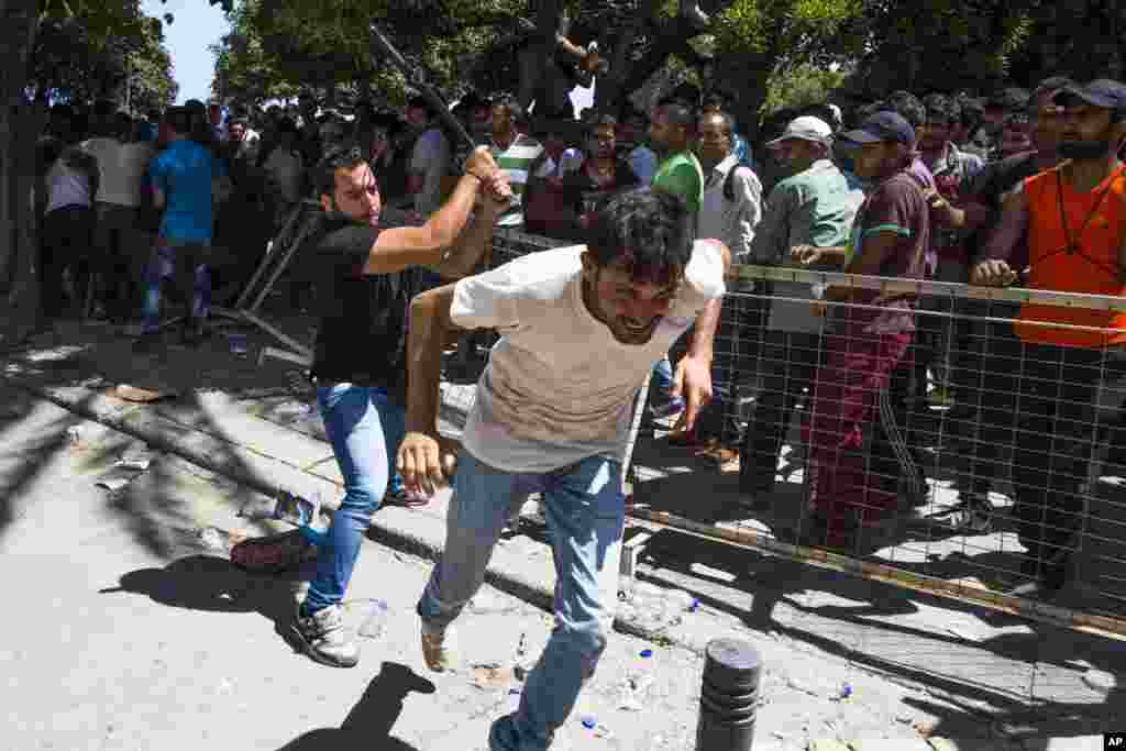 A Greek plain clothes policeman chases away Pakistani migrants as they started shouting while waiting to be registered near a police station at the southeastern island of Kos, Greece.