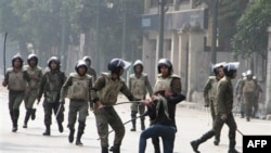 Binh sĩ Ai Cập bắt giữ một phụ nữ biểu tình gần trung tâm Quảng trường Tahrir ở Cairo