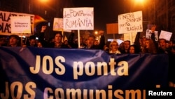 "People shout slogans and hold a banner reading ""Down Ponta, down communism"" in support of compatriots living abroad who were turned away as they tried to vote in the first round of a presidential election, during a rally in Cluj Nov. 8, 2014."