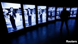 A visitor looks at screens showing Charlie Chaplin during a media tour of 'Chaplin's World', an interactive museum celebrating the life and works of the comic actor, in Corsier-sur-Vevey, Switzerland, April 16, 2016. The museum is set on the vast estate o