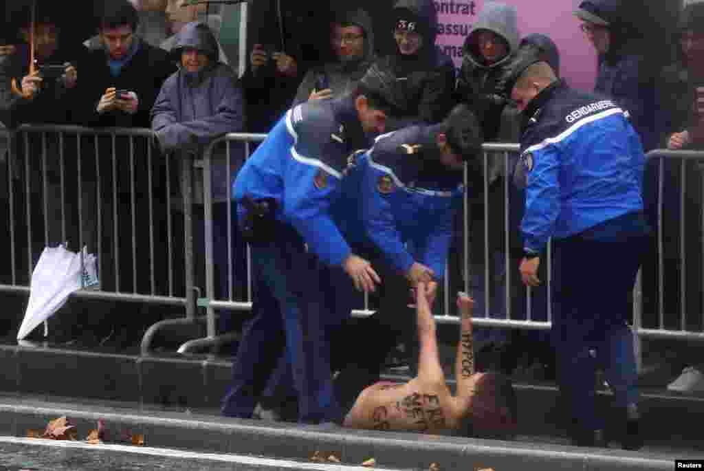 Petugas polisi menahan seorang demonstran perempuan (bertelanjang dada) yang mencoba melompat ke iring-iringan mobil Presiden AS Donald Trump dalam perjalanan untuk menghadiri peringatan 100 tahun berakhirnya Perang Dunia I di Arc de Triomphe, Paris, Perancis.