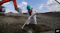Một công nhân, mặc đồ bảo hộ và mặt nạ, san đất tại nhà máy điện hạt nhân Fukushima Dai-ichi bị sóng thần làm tê liệt ở Okuma, Fukushima, đông bắc Nhật Bản, ngày 10 tháng 2 năm 2016.