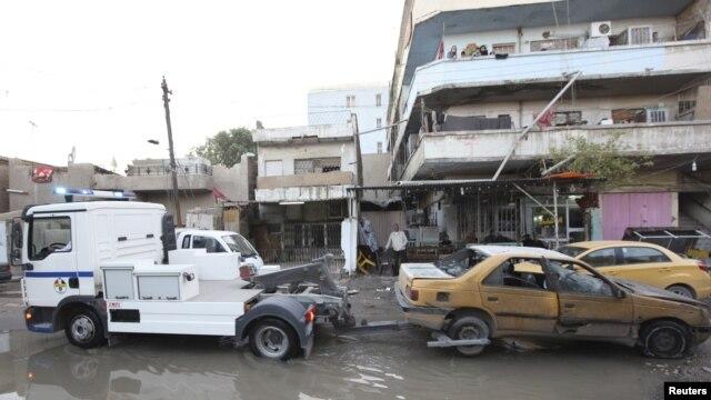 Một chiếc xe hơi bị hư hại trong vụ nổ bom ở quận Karrada, Baghdad, được kéo khỏi hiện trường, 31/12/12