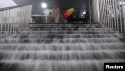 Nước lũ tràn xuống cầu thang ga xe điện ngầm ở Bắc Kinh, ngày 21/7/2012