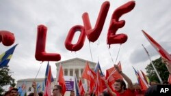 26일 미국 워싱턴의 연방대법원 앞에서 동성혼 지지자들이 '사랑'이라고 적힌 풍선을 날리며 동성혼 합헌 결정을 환영하고 있다.