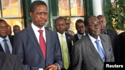 File - Zimbabwe President Robert Mugabe (R) and his Zambian counterpart Edgar Lungu step out of State House in Harare, February 2015.