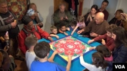 Children participate in the mandala dismantlement ceremony that follows the completion of the art. (VOA/ J. Soh)