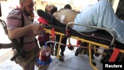Binh sĩ Syria giúp đỡ đồng đội bị thương sơ tán khỏi Aleppo, Syria, 1/8/2012