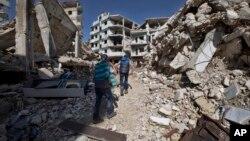 Des enfants syriens marchent entre les bâtiments détruits dans la vieille ville de Homs, en Syrie, le 26 février 2016. (AP Photo/Hassan Ammar)