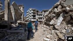 Trẻ em Syria đi bộ giữa các toà nhà bị phá huỷ ở thành phố Homs, Syria, ngày 26/2/2016.