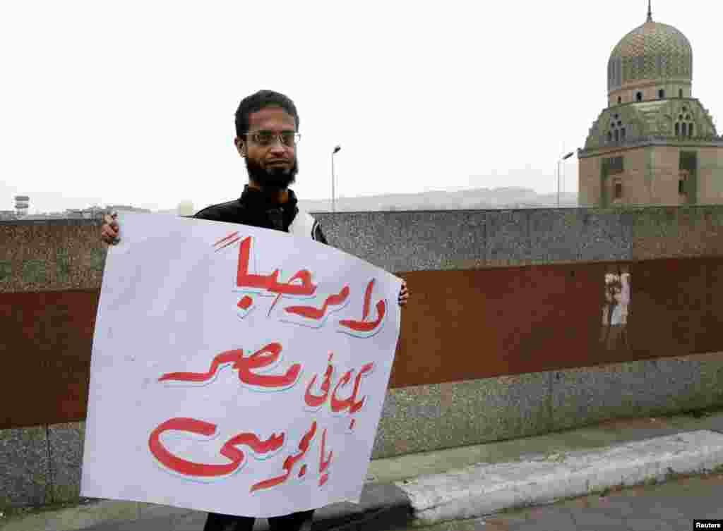 이집트 아즈하르 사원에서 이란 대통령의 방문에 반대하는 내용이 적힌 팻말을 들고 있는 남성.
