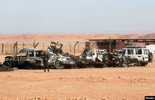 FILE - Algerian soldier stands near damaged cars used by Islamist militants during siege near the Tiguentourine Gas Plant, In Amenas, Jan. 31, 2013.