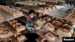 Seorang pegawai memeriksa topeng Donald Trump di sebuah pabrik di Jinhua, provinsi Zhejiang, China. (Foto: Ilustrasi)