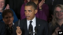 President Barack Obama holds up a pen as he speaks about the economy and the deficit in the East Room of the White House in Washington, file photo.