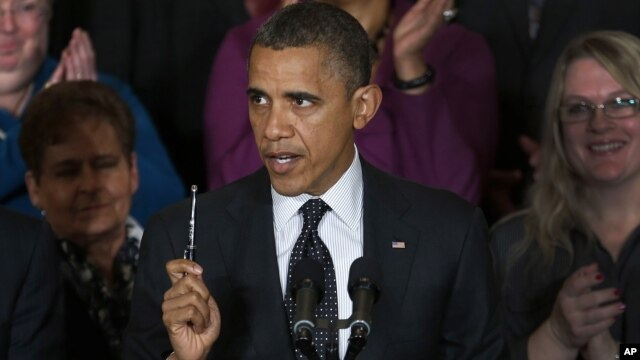 President Barack Obama holds up a pen as he speaks about the economy and the deficit in the East Room of the White House in Washington, November 9, 2012.