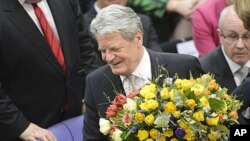 Joachim Gauck holds flowers after being elected president at Germany's Federal Assembly in Berlin, March 18, 2012.