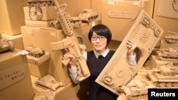 Artist Monami Ohno poses with several of her cardboard sculptures at a gallery event in Tokyo, Japan July 23, 2016. (Monami Ohno/Handout via REUTERS)