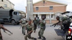 Government military officers runs outside the air-force base near the airport in Antananarivo, Madagascar, 20 Nov 2010