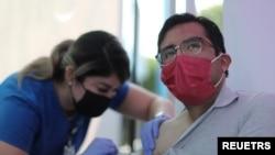 ARCHIVO - José Espinoza, de 27 años, recibe una vacuna contra la enfermedad del coronavirus en una clínica de vacunación COVID-19 en Los Ángeles, California, el 17 de agosto de 2021.