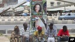 Wasu 'yan Nigeriake nan zaune a karkashin gada dauke da takardun gangamin zabe na Fasta a Ojuelegba jihar Ikkon Nigeria.
