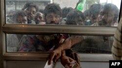 Para buruh migran antri untuk membeli tiket bus di Srinagar, Kashmir hari Rabu (7/8).