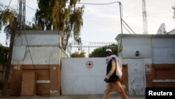 FILE - A man walks past the front gate of the International Committee of the Red Cross (ICRC) office in Jalalabad province, June 2, 2013