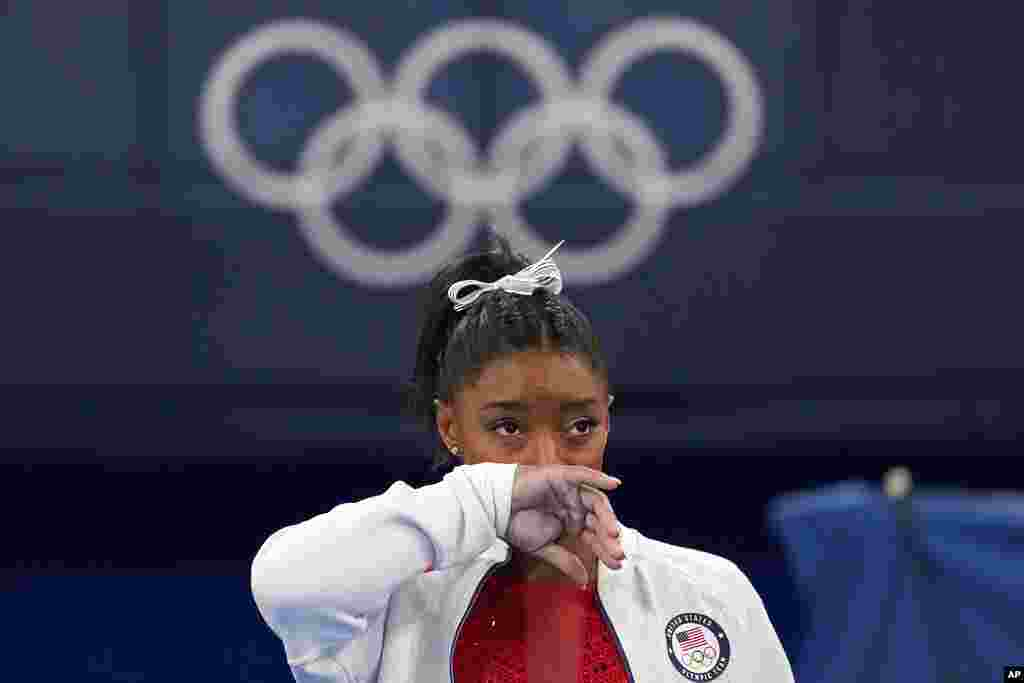 """Simone Biles of the United States watches gymnasts perform at the 2020 Summer Olympics, in Tokyo. Biles says she wasn't in right """"headspace"""" to compete and withdrew from the gymnastics team final."""