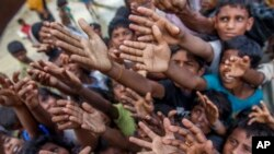 Rohingya Muslim children, who crossed over from Myanmar into Bangladesh, stretch their arms out to collect chocolates and milk distributed by Bangladeshi men at Taiy Khali refugee camp, Bangladesh, Sept. 21, 2017.