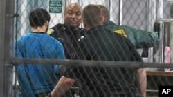 Esteban Santiago, présumé auteur de la fusillade à l'aéroport de Fort Lauderdale, tenu par des policiers, en Floride, 1er janvier 2017.