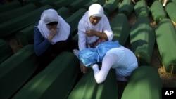 Porodice pored kovčega sa posmrtnim ostacima žrtava maskra u Srebrenici