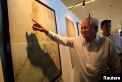 FILE - Philippine Foreign Secretary Albert Del Rosario points to an ancient map that officials said show that China's territorial claims over the South China Sea did not include the Scarborough Shoal.