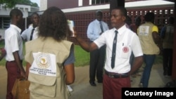 A student checks temperatures of students and visitors before schools open in Liberia