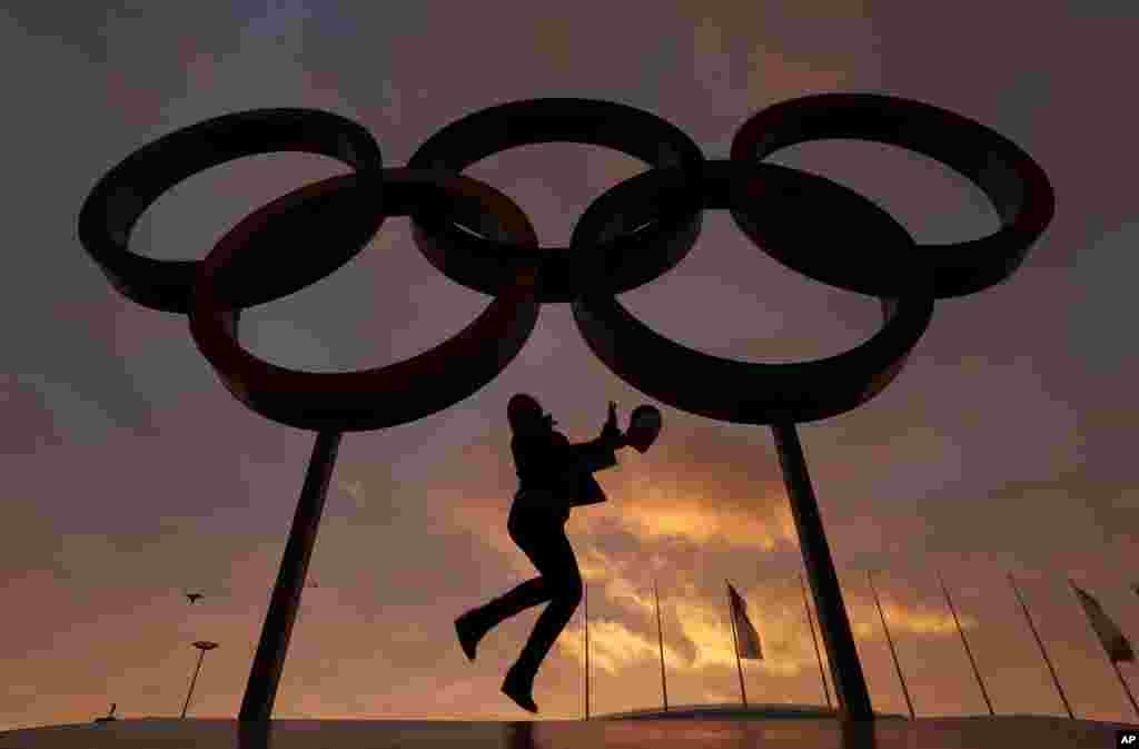 A woman poses with the Olympic rings in Olympic Park as preparations continue for the 2014 Winter Olympics, Feb. 5, 2014.