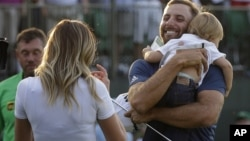 Dustin Johnson, right, greets his fiancée Paulina Gretzky as he holds their son Tatum Gretzky on the 18th hole during the final round of the U.S. Open golf championship at Oakmont Country Club on Sunday, June 19, 2016.