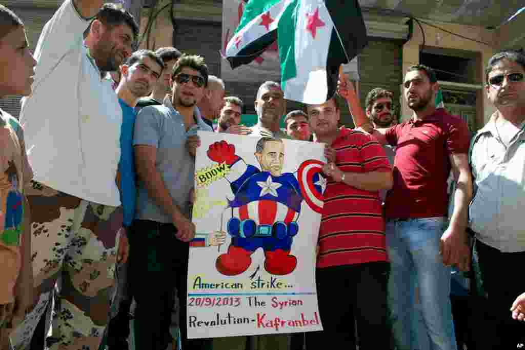 This citizen journalism image provided by Edlib News Network shows anti-Syrian regime protesters hold a poster depicting U.S. President Barack Obama during a demonstration in Kafr Nabil, Idlib province, Sept. 20, 2013.