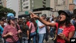 Un partidario del gobierno de Venezuela sostiene una copia de la Constitución del país mientras discute con opositores del gobierno que protestaban frente al Tribunal Supremo en apoyo a la Fiscal General Luisa Ortega Díaz y su rechazo a la convocatoria de la Asamblea Constituyente hecha por el presidente Nicolás Maduro.