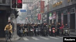 Local residents wait on motorcycles and bicycles at a traffic junction during a hazy day in downtown Shanghai, China, Dec. 6, 2013.
