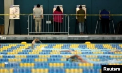 People vote on the deck of the Echo Park Deep Pool during the U.S. Presidential Primary Election in Los Angeles, California, June 7, 2016.