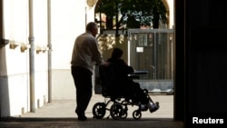 An elderly man pushes a woman in her wheelchair.