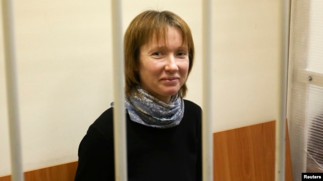 Yekaterina Zaspa, one of the 30 people who were arrested over a Greenpeace protest at the Prirazlomnaya oil rig, looks out from a defendants' cage as she attends a court session in St. Petersburg, Nov. 18, 2013.