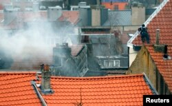 A masked Belgian policeman secures the area from a rooftop above the scene where shots were fired during a police search of a house in the suburb of Forest near Brussels, March 15, 2016. Teargas is seen at left.