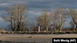 A flag and an obelisk mark the Civil War memorial on Hart Island in New York.