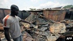 Một người đàn ông chỉ vào một cửa hàng bị đốt cháy gần Williamsville sau cuộc đụng độ giữa binh sĩ chính phủ và những chiến binh về phe ông Ouattara, ngày 15 tháng 3, 2011