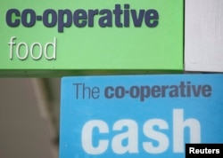 Signs are displayed outside of a branch of a Co-operative food store in north London, April 17, 2014.