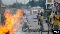 FILE - Protester stand by a burning barricade in the Musaga neighborhood of Bujumbura, Burundi, May 21, 2015.